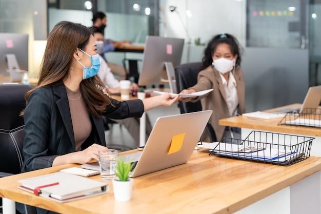 Группа межрасовых бизнес-работников носит защитную маску для лица в новом обычном офисе