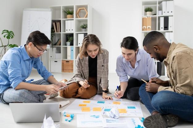 작업 보드와 함께 바닥에 앉아 사무실에서 마케팅 전략을 분석하는 인종 간 스타트 업 그룹