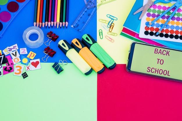 カラフルな背景、鉛筆、ノートブック、はさみ、スマートフォンの要素とメッセージの学校に戻るためのアイテムのグループ-教育コンセプト、コピースペース