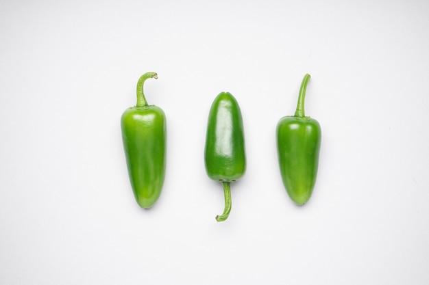 Группа перцев халапеньо на белом фоне, плоская планировка. зеленый перец чили.