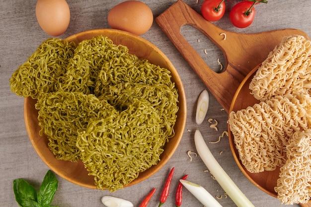 일본식 녹색 국수, mendake, 조리되지 않은 인스턴트 야채 또는 나무 절단 보드에 바삭한 건조 옥 국수의 그룹.