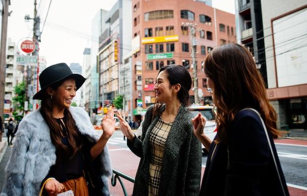 Группа японских женщин, проводящих время в токио, совершающих покупки в разных районах города