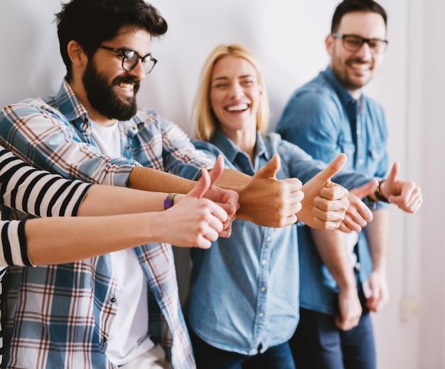 Группа радостных возбужденных молодых людей, поднявших палец вверх во время ожидания или перерыва. счастливая команда и концепция коллег.