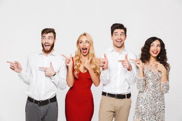 Группа радостных, умных одетых друзей, стоящих изолированно над белым, празднуя новый год, указывая пальцами в сторону