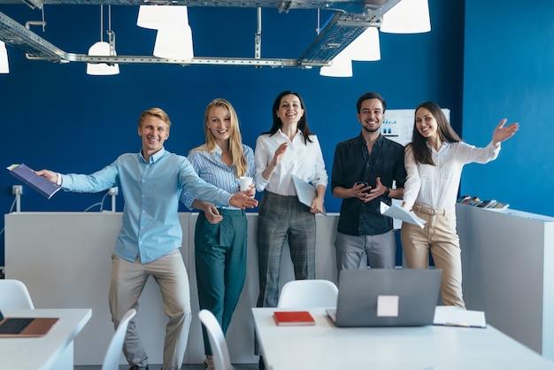 Группа радостных молодых людей, приветствующих с распростертыми объятиями