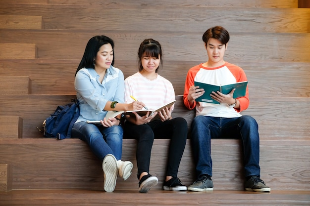 Группа младших и старших азиатских студентов, преподающих урок со своим преподавателем, концепция образования
