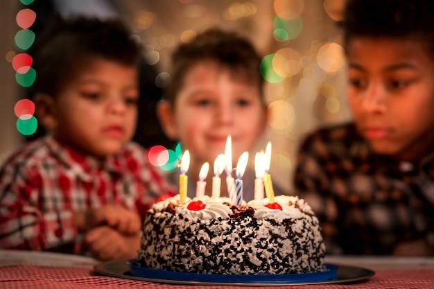 ケーキの男の子の横にある子供たちのグループがバースデーケーキの近くに座っています私たちのゲストはここで学校の友達の誕生日を訪れています...