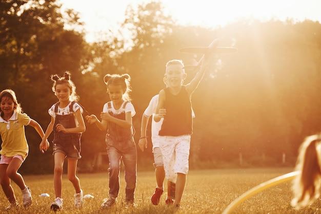 아이들의 그룹은 현장에서 활동적인 주말을 보내고 있습니다. 아름다운 햇빛에 의해 조명.