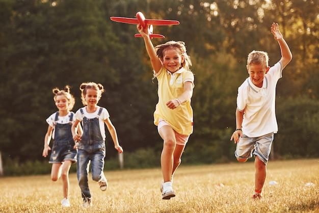 빨간 장난감 비행기를 손에 들고 야외에서 즐거운 시간을 보내는 아이들.