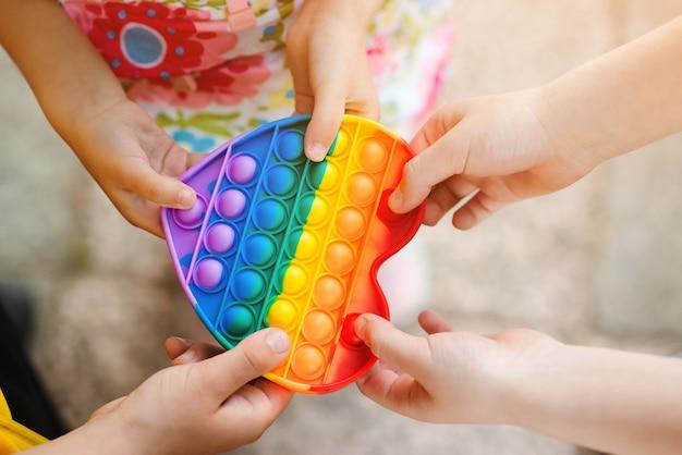 Группа детей держит популярную игрушку, вид сверху. счастливые дети веселятся на открытом воздухе.