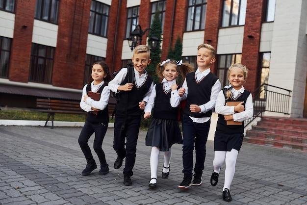 교복을 입은 아이들이 교육 건물 근처에서 함께 야외에서 카메라를 향해 포즈를 취했습니다.
