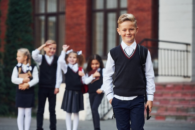 Группа детей в школьной форме вместе позирует перед камерой на открытом воздухе возле здания образования.