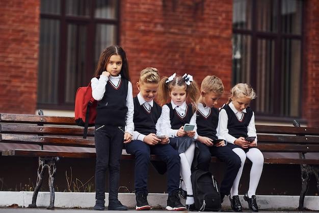 制服を着た子供たちのグループが、教育棟の近くの屋外のベンチに一緒に座っています。