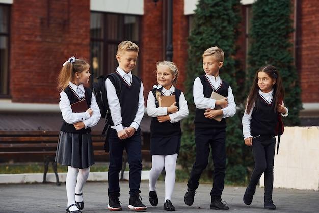 교육 건물 근처에서 함께 야외에 있는 교복을 입은 아이들 그룹.
