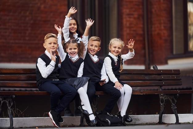 教育棟の近くで一緒に屋外にある制服を着た子供たちのグループ。