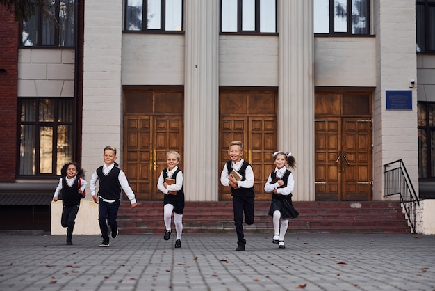 야외에서 함께 달리는 교복을 입은 아이들 그룹.