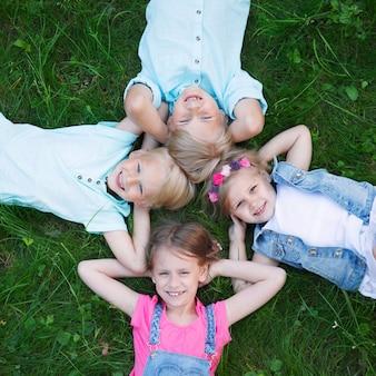 Группа детей, лежащих на траве