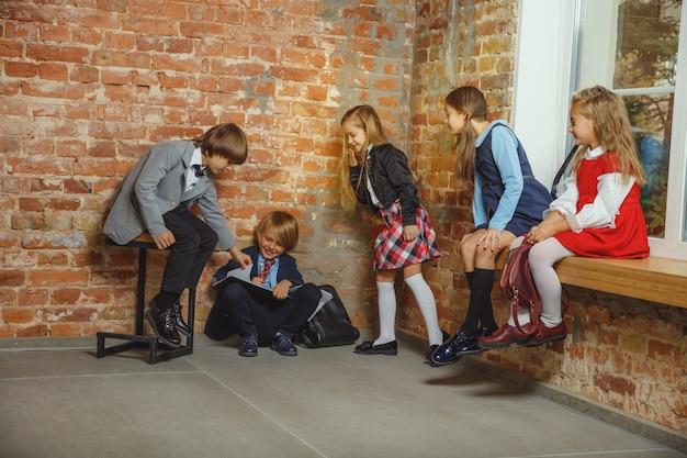 함께 방과 후 시간을 보내는 아이의 그룹입니다. 숙제를 시작하기 전에 수업 후 쉬고 잘 생긴 친구. 현대 다락방 인테리어. 학교 시간, 우정, 교육, 공생 개념.