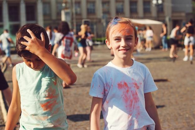 Группа детей, бросая красочный порошок в воздух. празднование холи. друзья веселятся во время праздника холи. счастливое детство. предварительно мальчики-подростки, играющие с цветами. концепция индийского фестиваля холи.