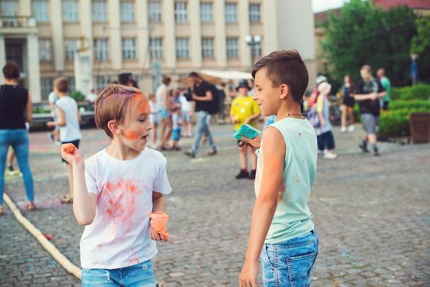 空中にカラフルな粉を投げる子供たちのグループ。ホーリー祭。ホーリー祭の間に楽しんでいる友達。幸せな子供時代。色で遊んでいる10代前の男の子。インドのお祭りホーリーのコンセプト。