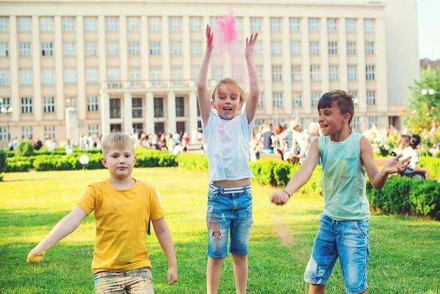 空中にカラフルな粉を投げる子供たちのグループ。ホーリー祭。ホーリー祭の間に楽しんでいる友達。