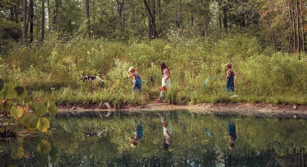 緑に覆われ、日光の下で湖に反射してフィールドを歩く子供たちのグループ