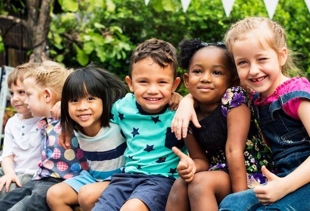 Группа детского сада дети друзья руки вокруг сидя и улыбается весело
