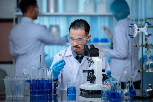 Группа лаборантов проверяет кровь с помощью микроскопа и делает тест на бактерии