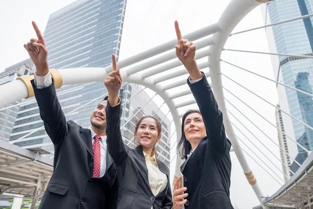 Группа лидеров бизнеса, стоящая и указывая пальцем в будущее