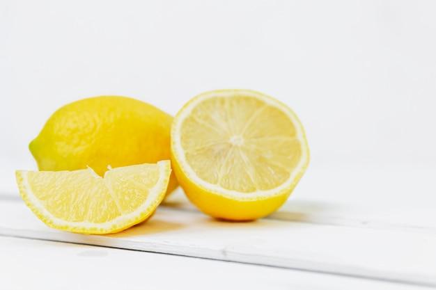 Группа лимонов: целый, половина и ломтик на белой стене. пространство для текста. витамины и здоровое питание.