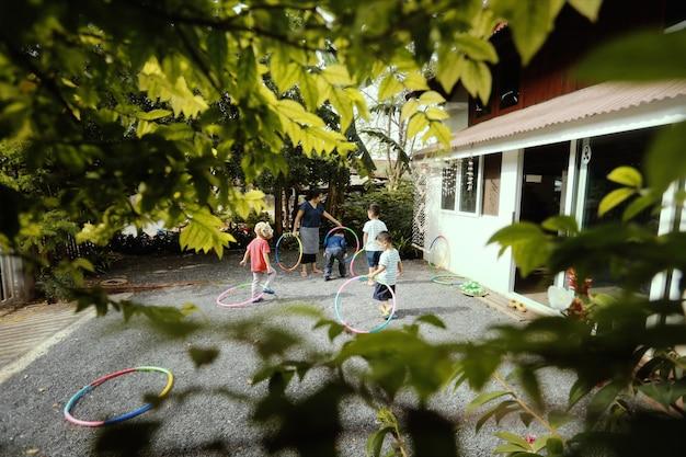 庭、ホームスクール、ウォルドルフ教育の概念で遊ぶ小さなアジアの子供たちのグループ。