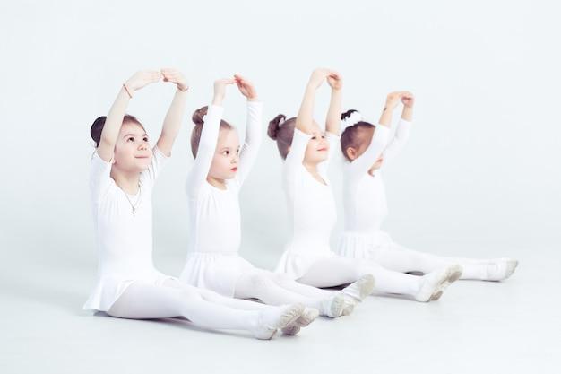 Группа маленьких девочек занимается в балетной школе