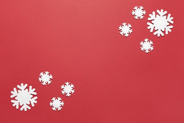 Группа маленьких белых чувствовал снежинки на бордовый красный, копией пространства.
