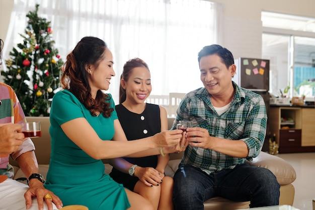 自宅で小さなパーティーを開き、お茶を飲み、ニュースについて話し合う成熟したアジアのカップルのグループ