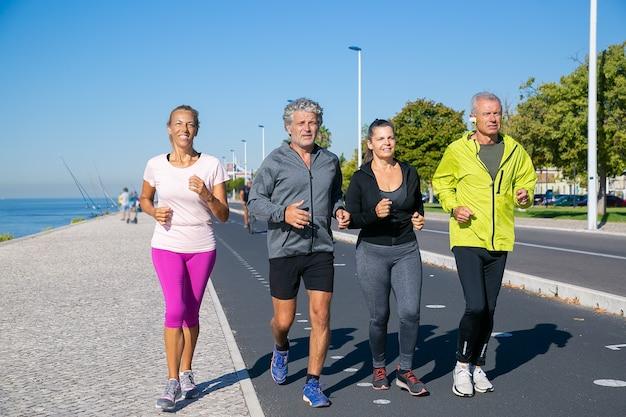 Группа зрелых людей в спортивной одежде, бег по берегу реки. кадр в полный рост. концепция выхода на пенсию или активного образа жизни