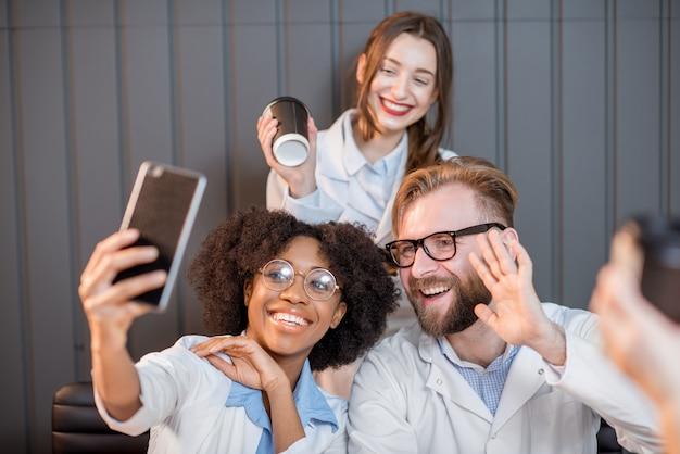 교실에서 커피를 마시는 동안 휴대폰으로 즐겁게 사진을 찍고 있는 의대생 그룹