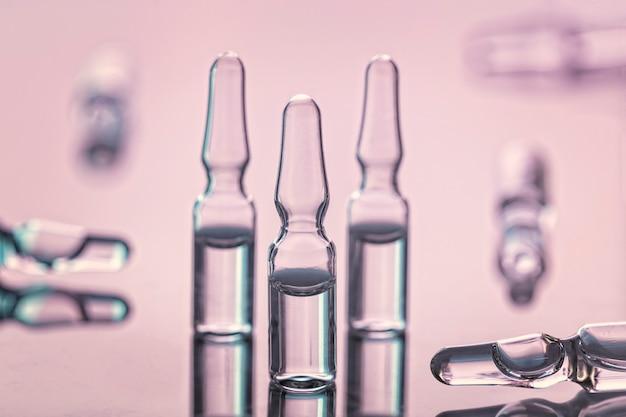 Группа медицинских стеклянных ампул с отражениями, на розовой стене