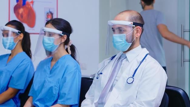Группа медицинского персонала, сидящего в зоне ожидания больницы, в маске и козырьке от коронавируса. врач с белым халатом и стетоскопом. пациент выходит из клиники.
