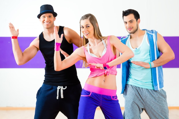 ダンススクールでズンバフィットネスの振り付けを踊る男性と女性のグループ