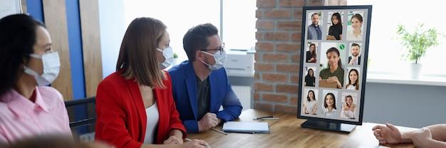 Группа мужчин и женщин сидят за столом в защитных масках и смотрят на конференц-компьютер