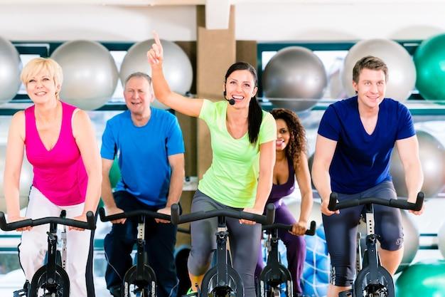 Группа мужчин и женщин, вращающихся на фитнес-велосипедах в тренажерном зале