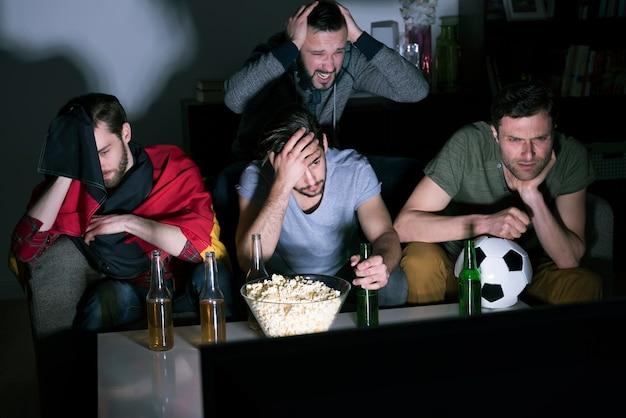 ビールを飲み、テレビでサッカーを見ている男性のグループ