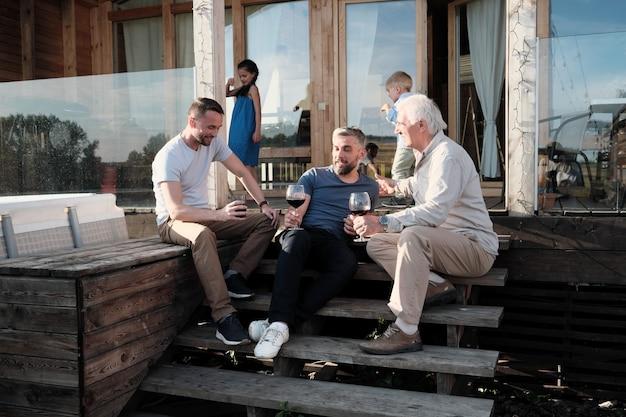 Группа мужчин сидит на крыльце, разговаривает друг с другом и пьет красное вино, отдыхая за городом на открытом воздухе