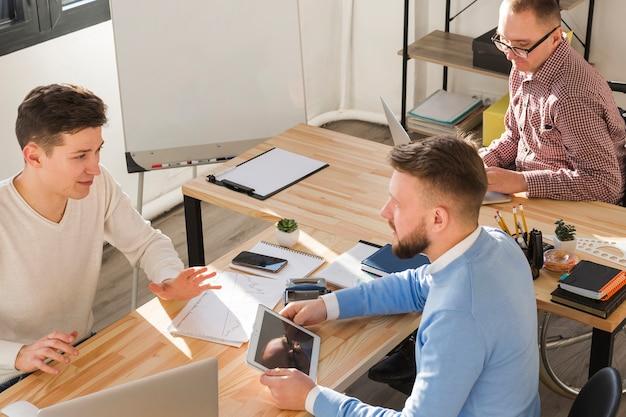 Группа мужчин, работающих вместе в офисе