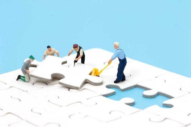직소 퍼즐을 조립하는 소형 사람들의 그룹입니다. 비즈니스 팀워크 개념입니다.