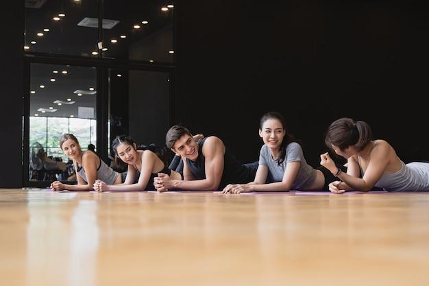 스튜디오 체육관에서 코브라 포즈를 위해 요가를 하는 여성과 남성 모두 백인과 아시아인의 혼합 인종 그룹, 요가 및 피트니스는 건강 관리 개념을 운동합니다.