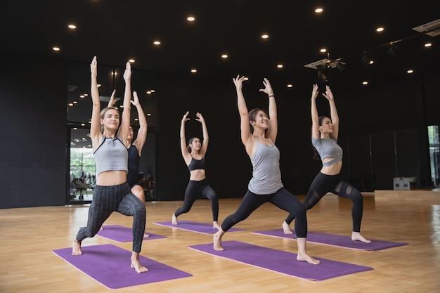 Группа смешанной расы кавказских и азиатских людей, женщин и мужчин, практикующих йогу, позируют в тренажерном зале студии