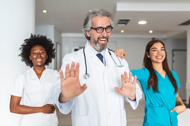 並んで立ってカメラを見ている混合年齢の医師と看護師のグループ。