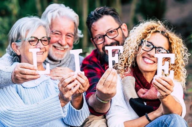笑顔でブロック文字を人生の言葉で示している混合年齢世代の人々のグループ-家族のように一緒にアウトドアレジャー活動を楽しんでいる幸せなライフスタイル