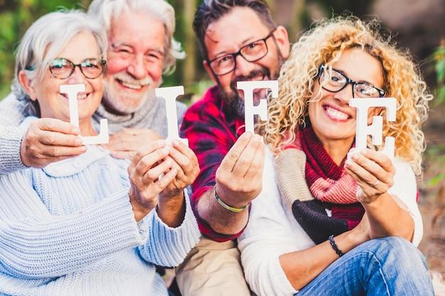 混合年齢の人々のグループは、ブロックと笑顔で人生を祝います